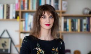 Gemma Carey stands in front of a bookshelf facing the camera