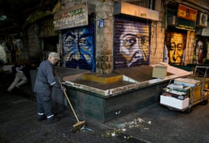 A cleaner sweeps next to graffiti portraits painted on the closed shutters of stalls