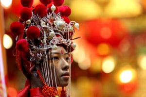 A girl poses for photos at a temple during the Chinese Lunar New Year celebration in the Chinatown of Yangon, Myanmar