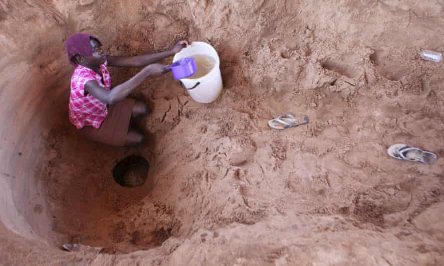 A woman fetches drinking water from a well in Zimbabwe