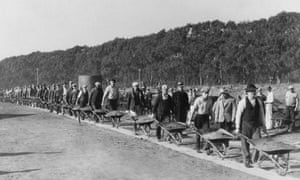 Public Works Administration workers fill a gully with wheelbarrows of earth during the construction of the Lake Merced Parkway Boulevard, under President Franklin D. Roosevelt's New Deal, San Francisco, California, 1934.
