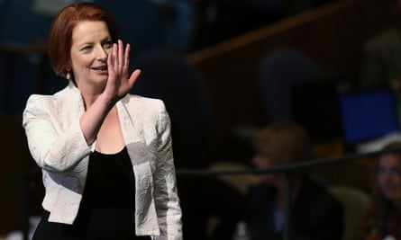 Julia Gillard in a public forum, smiling and with her hand raised