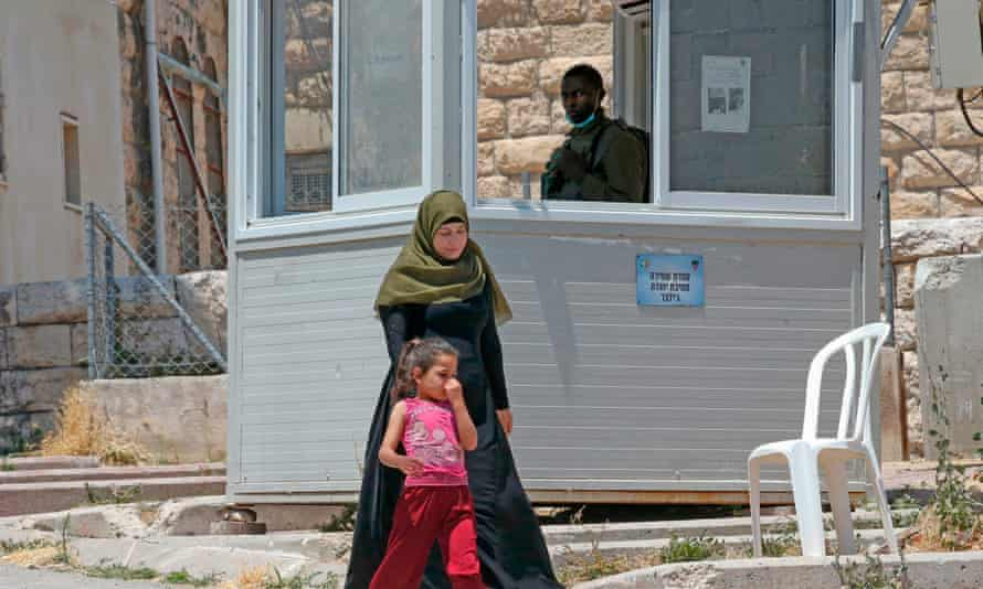 Palestinians walk past an Israeli military guard post to reach their homes.