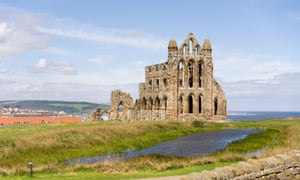 Exterior Whitby Abbey in North Yorkshire on a bright, blue sky day.