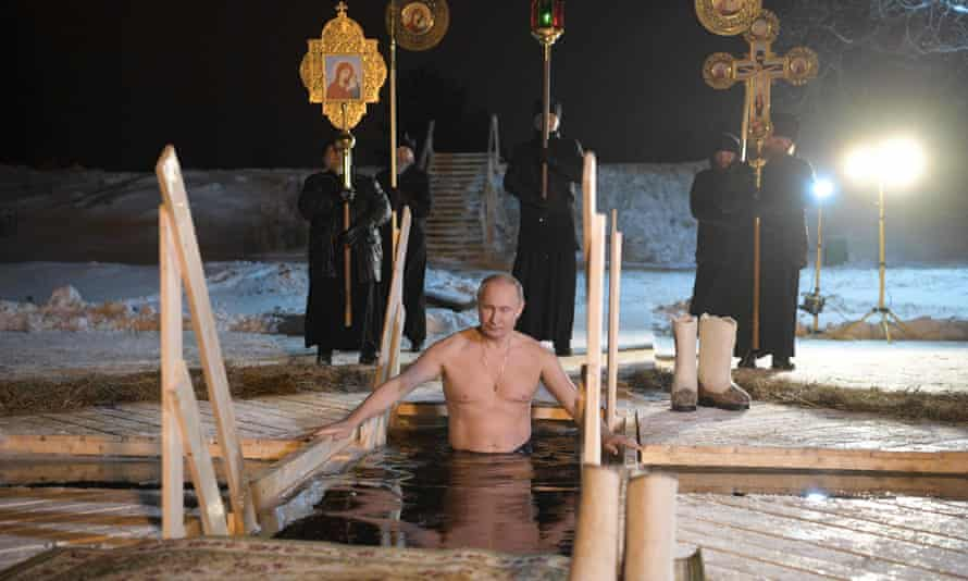 Putin takes the plunge at icy Lake Seliger during Epiphany, lifeguards in attendance.