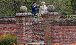 Shinzo Abe and Theresa May walk in the garden at Chequers.