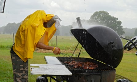 man grilling chicken in the rain