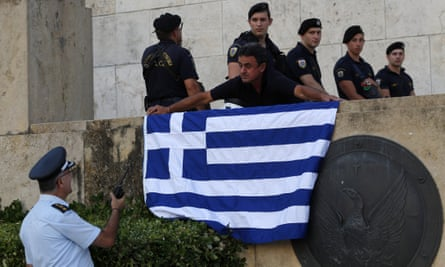 An anti-austerity protester places a Greek flag next to an entrance to the Greek parliament