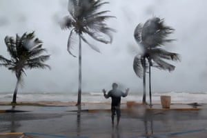 A man stands in the winds and rain in Luquillo, Puerto Rico, on Wednesday as the storm approaches.
