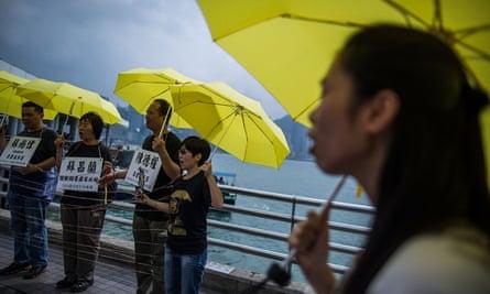 people holding yellow umbrellas on  Tsim Sha Tsui Pier  in  Hong Kong