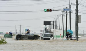 People wait for help on the roofs of their submerged vehicles