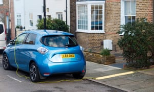 electric car being charged in street with lead from owners home