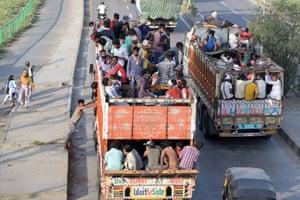 Migrant workers travel on trucks in Prayagraj
