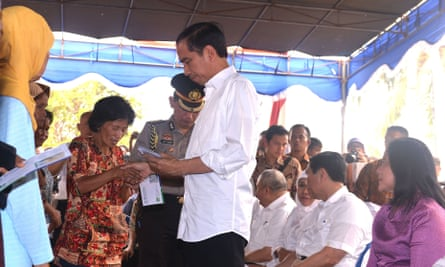 Indonesian president Joko Widodo, centre, hands out healthcare cards and compensation to families affected by the haze in South Sumatra.