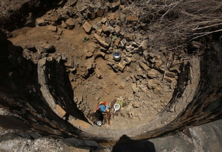 An Indian woman tries to collect drinking water in a dried-up well at Bhakrecha Pada in Thane district in Maharashtra state, India