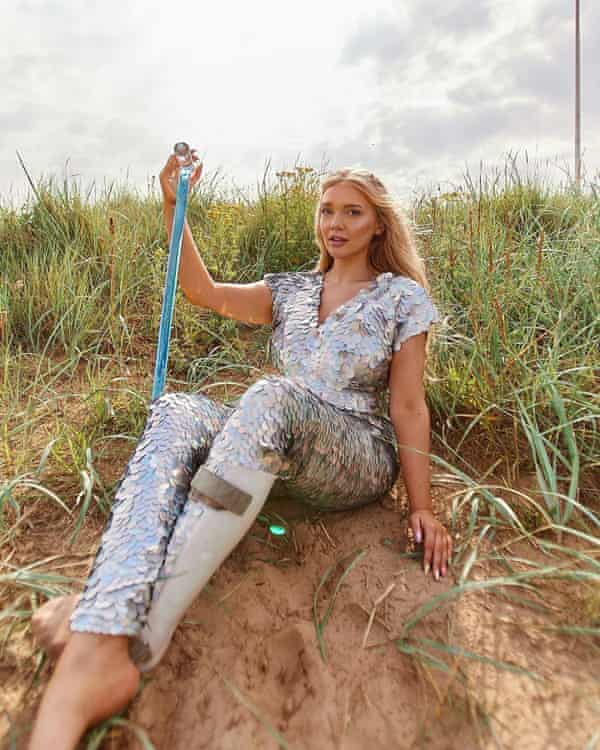 Lucy Dawson sitting in sand dunes wearing a silver scaled suit like a mermaid and holding a blue walking stick