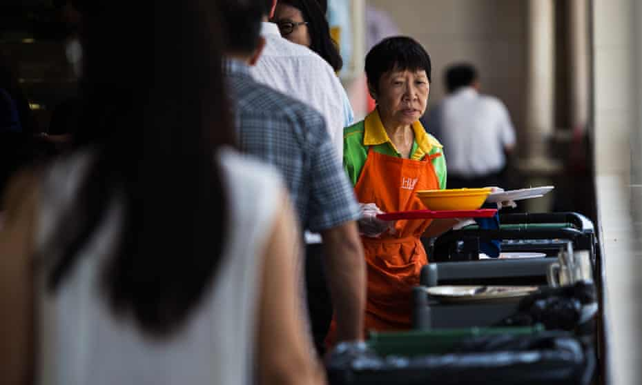 An employee collects used dishes at a food centre in Singapore.
