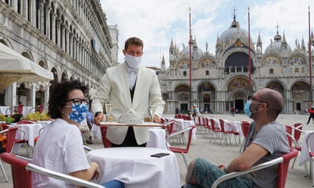 A waiter serves two tourists at the outdoor tables of the 'Caffe Quadri' on St Mark's square.