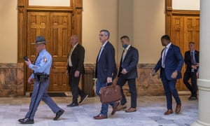 Brad Raffensperger, the Georgia secretary of state, center, leaves the state capitol building after reports of threats on 6 January.