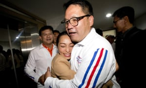 A supporter hugs Palang Pracharat party leader Uttama Savanayana after it took the lead in Thailand's first election since 2014