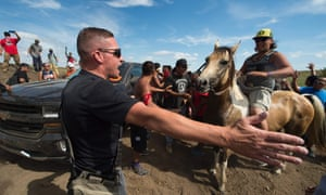 Native American protesters and their supporters are confronted by security during a demonstration against work being done for the Dakota Access Pipeline.