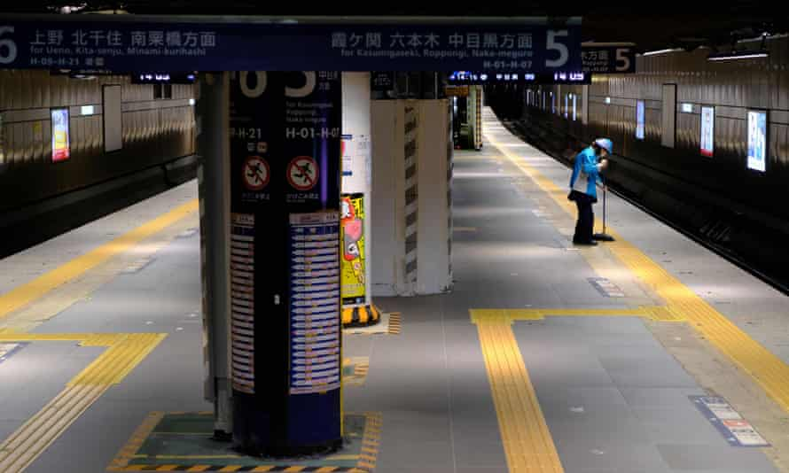 A worker cleans up the platform at Ginza subway station in Tokyo