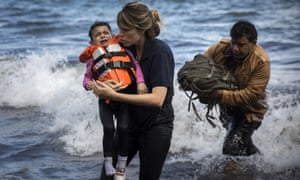 Lesbos volunteer holds Syrian child