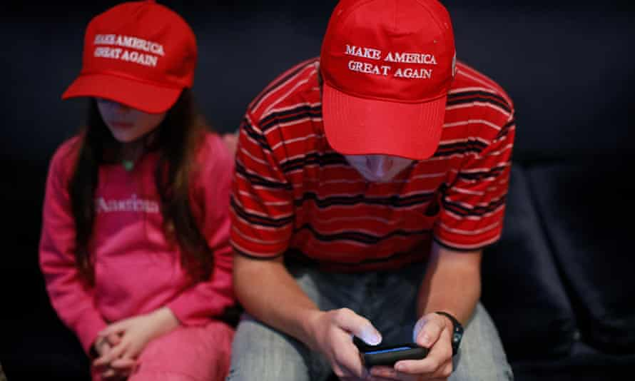 A supporter checks his phone at a rally for Republican Mike Braun in Indiana.