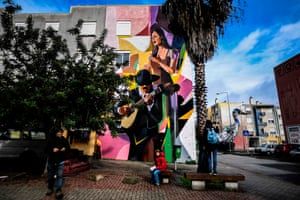Visitors take pictures of a murals by Russian artist Zmock (left) and Portuguese artist Bordalo II (right) during a guided visit to Quinta do Mocho