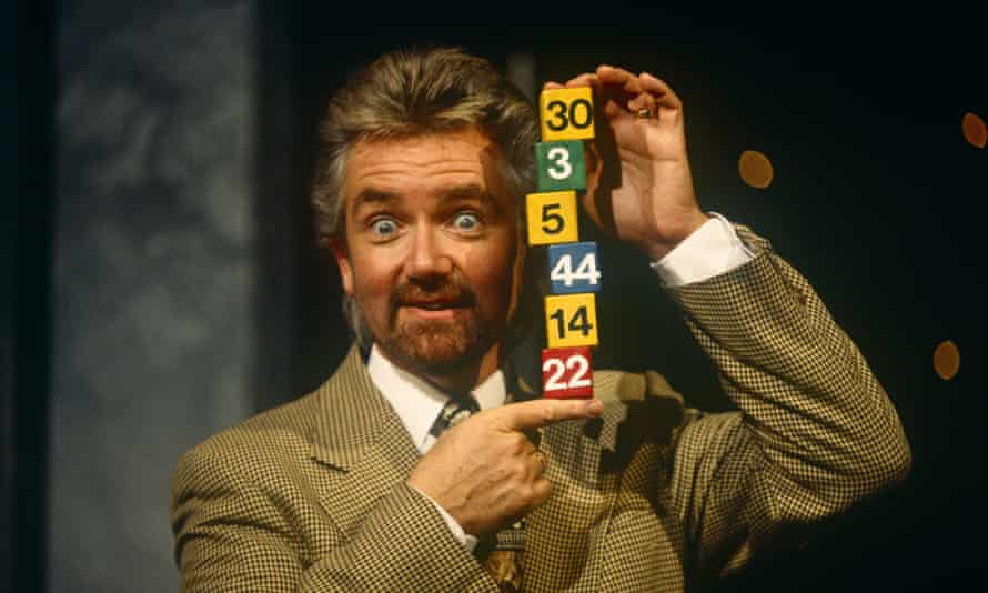Noel Edmonds in a jacket and tie holding up a stack of lottery numbers on cubes