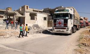 Syrian children watch aid trucks drive through a village