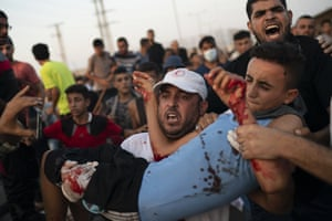 A young Palestinian protester is carried to an ambulance after being shot during a protest at the entrance of the Erez border crossing between Gaza and Israel.