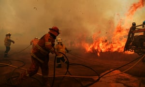 The death toll from bushfires in NSW and Queensland has risen to four. Firefighters battle a spot fire at Hillville, New South Wales.