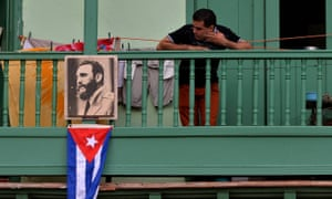 A man remains in a balcony next to a picture of Cuban revolutionary leader Fidel Castro at San Francisco de Asis Square in Havana.