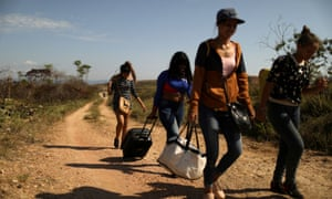 Venezuelan migrants walk along a trail into Brazil, at the border city of Pacaraima, Brazil, on 11 April 2019.