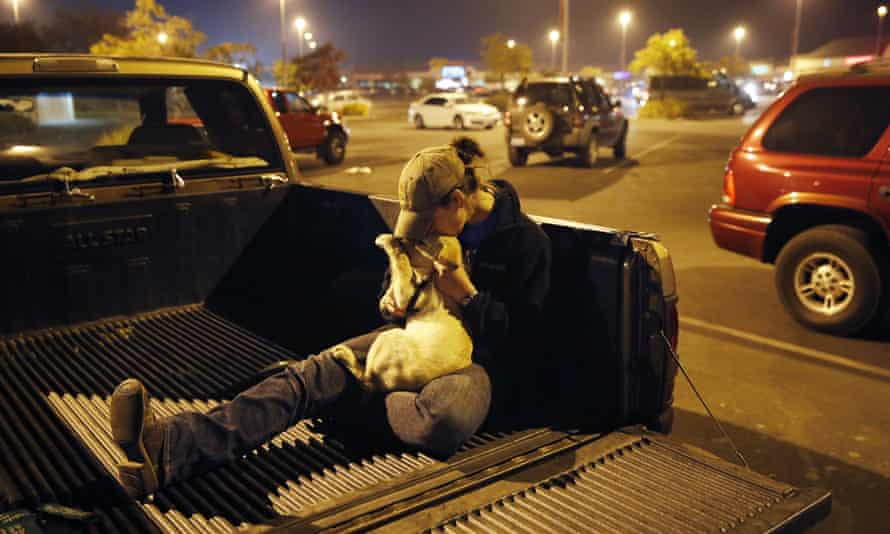 Sarah Gronseth kisses her dog Branch in a parking lot in Chico. Gronseth, a teacher, evacuated some of her high school students in her truck as the fire bore down on the high school in Paradise.