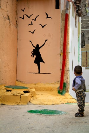 A boy admires some of the street art that adorns many of the camp's walls