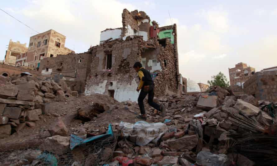 A Yemeni boy runs past buildings that damaged by Saudi-led airstrikes on March 23 in Sana'a.