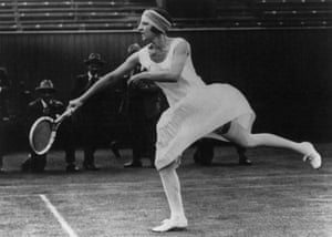 """French player Suzanne Lenglen – winner of six Wimbledon titles – broke with the corsets and petticoats of old. It didn't go unnoticed. When, in 1919 she competed in a short-sleeved, calf-length dress with no petticoat, eyebrows were apparently raised. But her style, including her customary thick headband, also won her many fans. In 1926, Vogue described how: """"The French champion wears a tennis costume that is extraordinarily chic in the freedom, the suitability, and the excellence of its simple lines."""""""