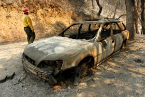 Tom Stokesberry with the U.S. Forest Service walks past a destroyed car