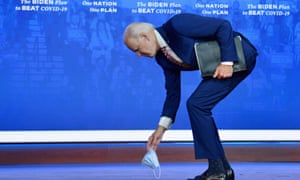 Democratic presidential nominee and former Vice President Joe Biden picks up his mask after dropping it at the end of his speech on Covid-19 at The Queen theater on October 23, 2020 in Wilmington, Delaware.