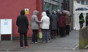 People queue for a Covid vaccine in outside Hornchurch library in Havering, London