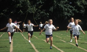 Children race on a green field for sports day