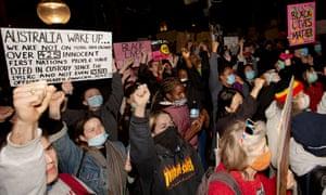Протестующие, одетые в защитные маски для лица и держащие плакаты, маршируют к зданию парламента от фонтана Арчибальда в Гайд-парке 2 июня 2020 года в Сиднее, Австралия.