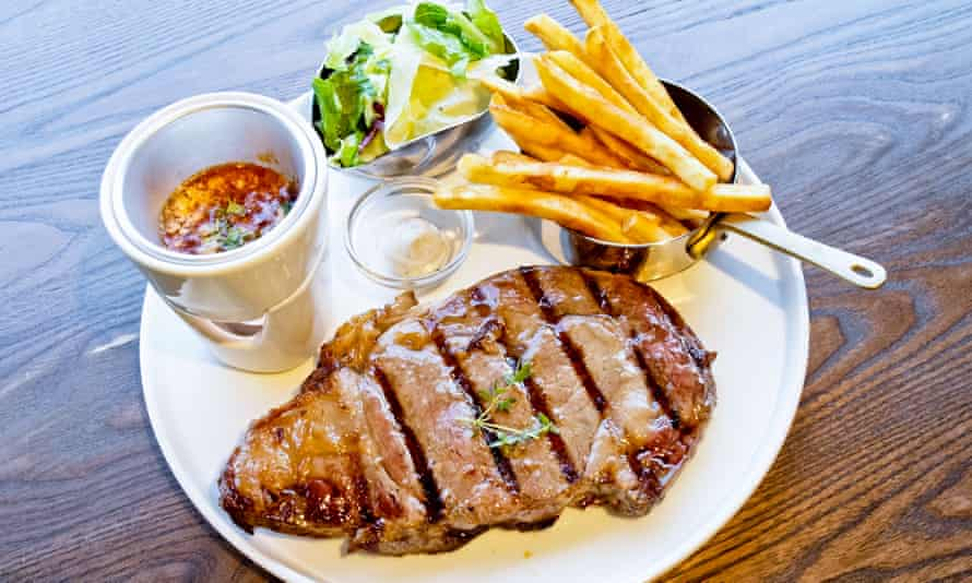 Rib-eye steak with salad and fries.