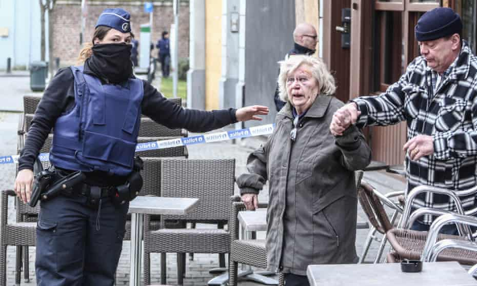 A police officer evacuating bystanders at the scene of Tuesday's raid in Brussels. Three officers were injured during the operation.