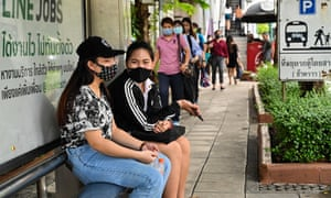 People wait at a bus stop in Bangkok on 18 June 2020.
