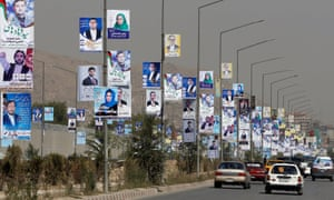 Election posters for parliamentary candidates line a road in Kabul.