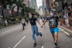 Protesters run away as police fire water cannon and pepper spray at the crowd