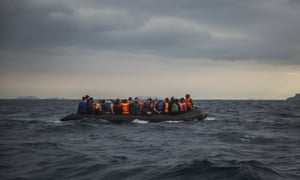 Refugees and migrants onboard a dinghy approach the Greek island of Lesbos after crossing the Aegean sea from Turkey.